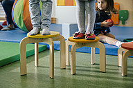 Feet of two children standing on chairs of different heights in kindergarten - MFF04055