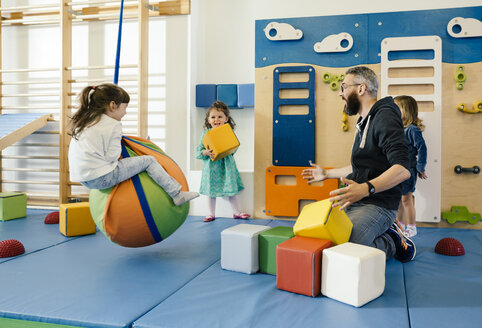 Pre-school teacher and happy children playing in gym room in kindergarten - MFF04058