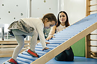 Pre-school teacher watching little girl walking upwards - MFF04061
