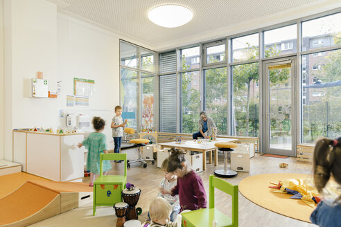 Pre-school teacher and children in playing in learning room in kindergarten - MFF04079