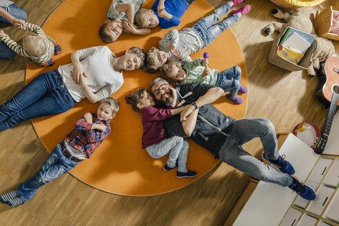 Children and teachers lying on carpet in kindergarten - MFF04085