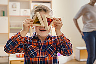 Boy holding wooden and colorful blocks before his eyes in kindergarten - MFF04088
