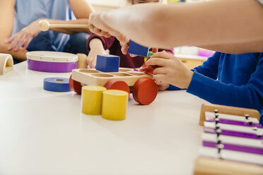 Close-up of children playing with musical instruments and toys in kindergarten - MFF04091
