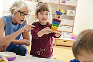 Pre-school teacher and child playing with wooden toys in kindergarten - MFF04094