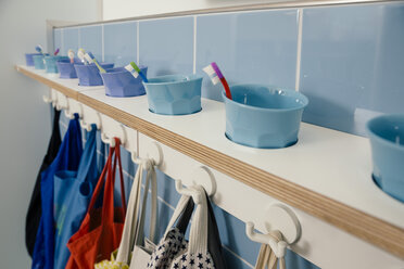 Line-up of of toothbrushes and bags on hooks in kindergarten - MFF04097