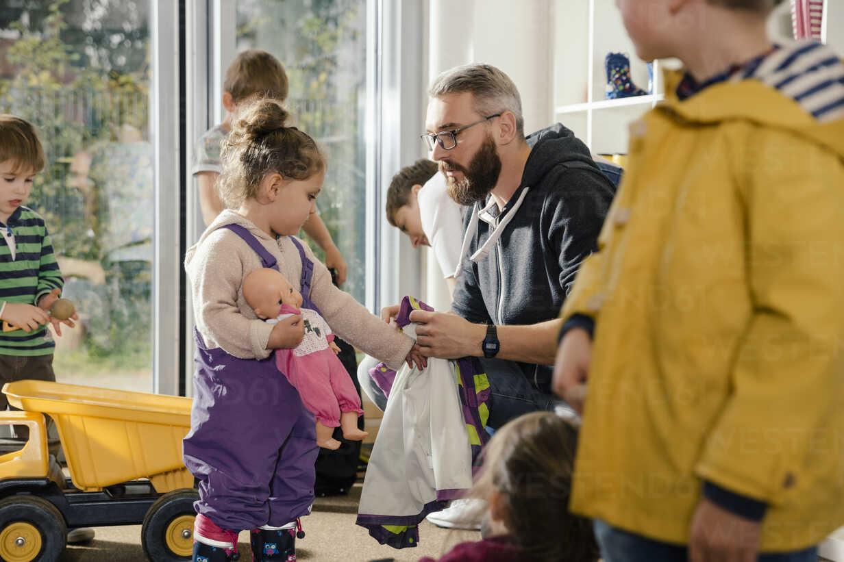 Pre-school teacher helping girl putting on rainwear in kindergarten - MFF04106 - Mareen Fischinger/Westend61