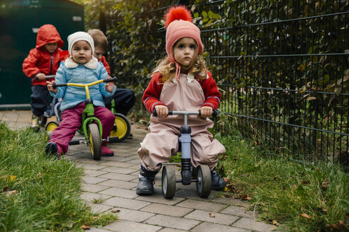 Children using scooters in garden of a kindergarten - MFF04115