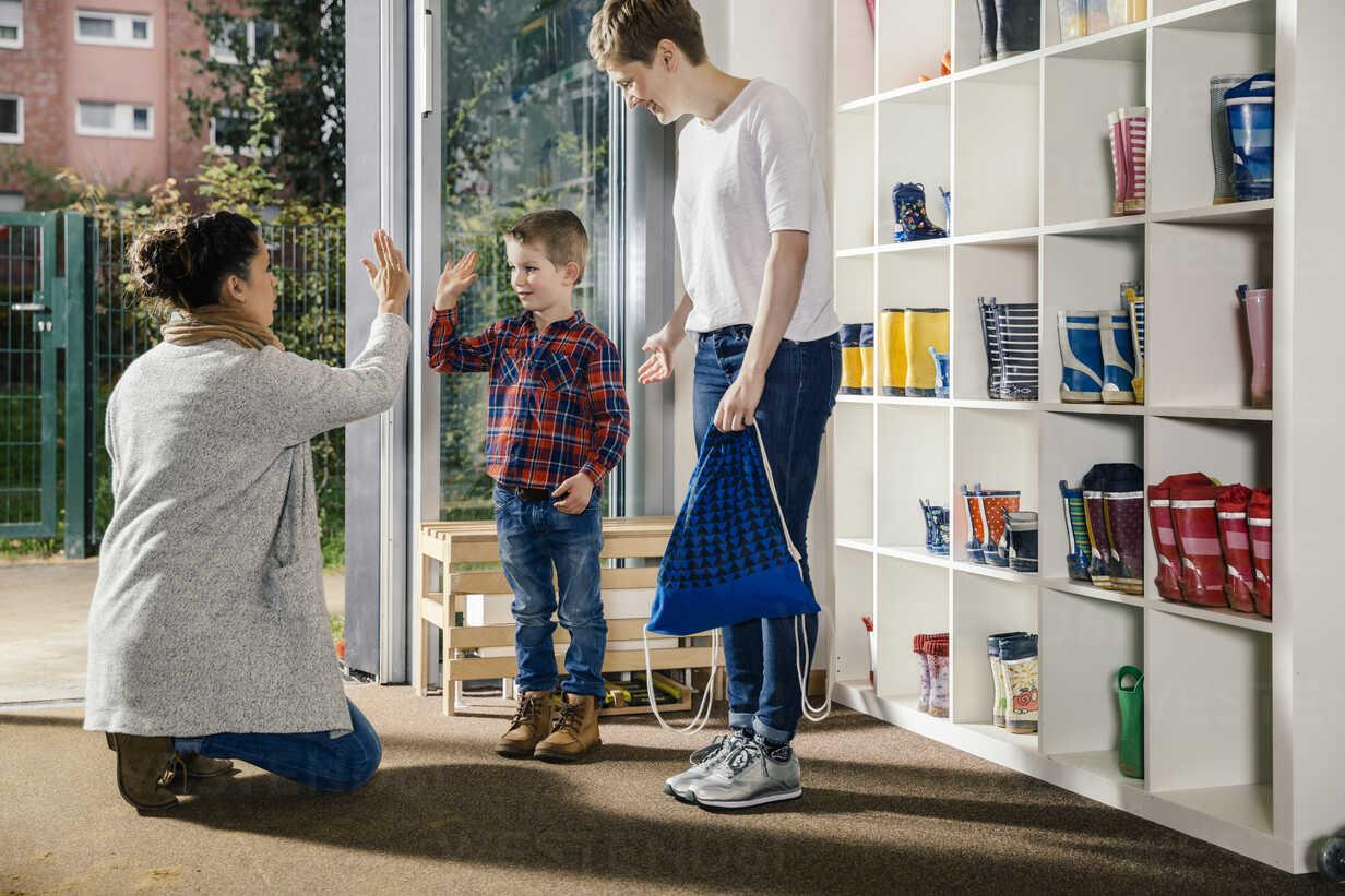 Boy high fiving with mother in kindergarten - MFF04118 - Mareen Fischinger/Westend61
