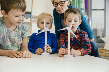 Boys and pre-school teacher looking at wind turbine models in kindergarten - MFF04127