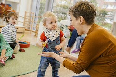 Pre-school teacher playing with little boy in kindergarten - MFF04139