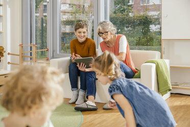 Pre-school teachers with tablet looking at children in kindergarten - MFF04142