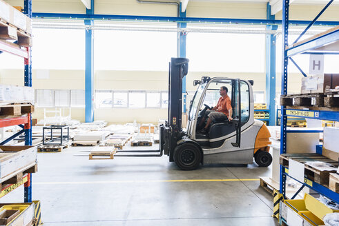 Man on forklift in factory warehouse - DIGF03166