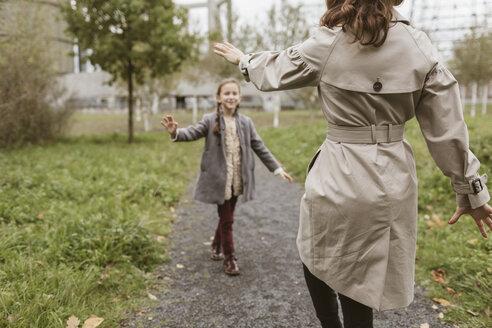 Mother and little daughter dancing on walkway - KMKF00051