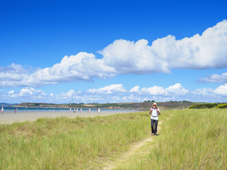 France, Bretagne, Active senior hiking on the beach of Treguer - LAF01932