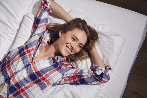 Portrait of laughing woman lying on bed with hands behind her head - PNEF00257
