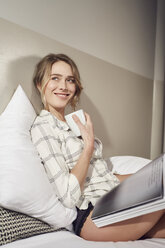 Portrait of smiling woman sitting on bed with coffee mug and magazine - PNEF00260