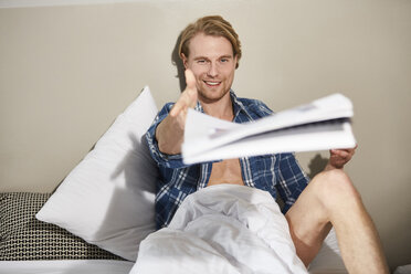 Portrait of smiling young man sitting on bed throwing newspaper - PNEF00266