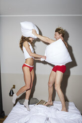 Couple having a pillow fight in bed - PNEF00272