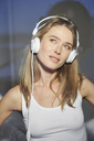 Portrait of woman behind windowpane listening music with headphones - PNEF00278