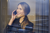 Portrait of laughing businesswoman on the phone behind windowpane - PNEF00281