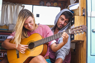 Young couple with guitar in a van - SIPF01836