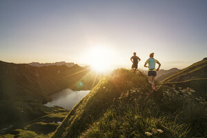 Germany, Allgaeu Alps, man and woman running on mountain trail - MALF00007