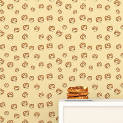 Plate with pretzels on cup board in front of wallpaper with pretzel pattern, 3D Rendering - UWF01307