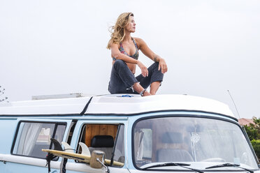 Spain, Tenerife, young woman relaxing on car roof of van - SIPF01847