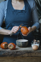 Woman peeling persimmon for preparing dessert, partial view - ALBF00185