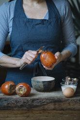 Woman peeling persimmon for preparing dessert, partial view - ALBF00185
