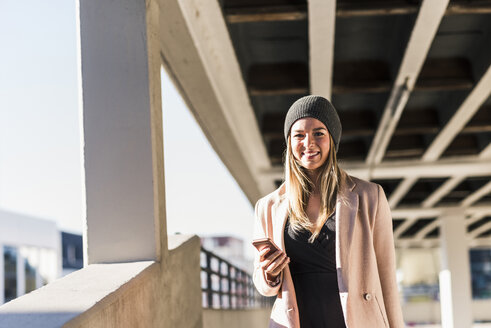 Smiling young woman with cell phone wearing wooly hat - UUF12213