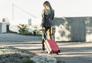 Young woman with rolling suitcase in the city - UUF12225