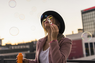 Young woman in the city blowing soap bubbles in the evening - UUF12240