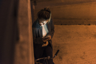 Young woman in the city checking cell phone at night - UUF12246