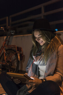 Smiling young woman in the city using tablet at night - UUF12252