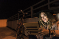 Smiling young woman in the city using tablet at night - UUF12255