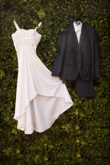 Wedding dress and suit of groom hanging at green wall - FCF01299