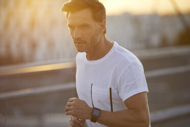 Man with smartwatch running in the city - PNEF00298