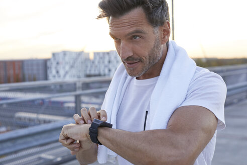 Athlete in the city with smartwatch and towel - PNEF00301