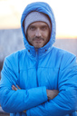 Portrait of confident man with hooded jacket and wooly hat in the city - PNEF00304