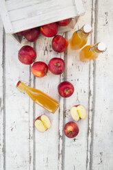 Bottle and glass of apple juice, red apples on wood - LVF06409