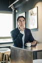 Businessman in cafeteria with cup of coffee thinking - JOSF01806