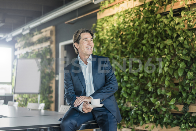 Laughing businessman in green office with cup of coffee - JOSF01815