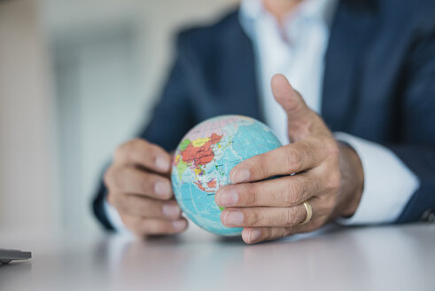 Close-up of hands of businessman holding globe - JOSF01830