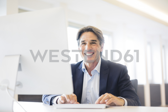 Portrait of happy businessman working at desk in office - JOSF01836