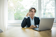 Businessman using laptop at table in office - JOSF01845