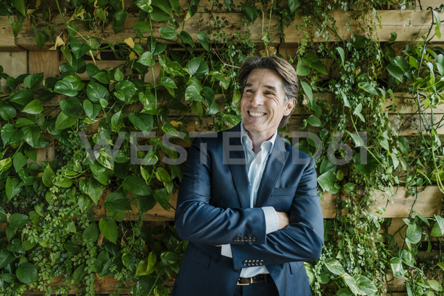 Smiling businessman in green office - JOSF01860