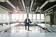 Businessman sitting on table in conference room - JOSF01863