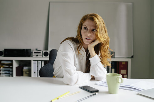 Young woman with cup of coffee at desk in office - BMF00865