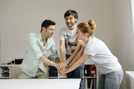 Happy colleagues in office stacking hands - BMF00880